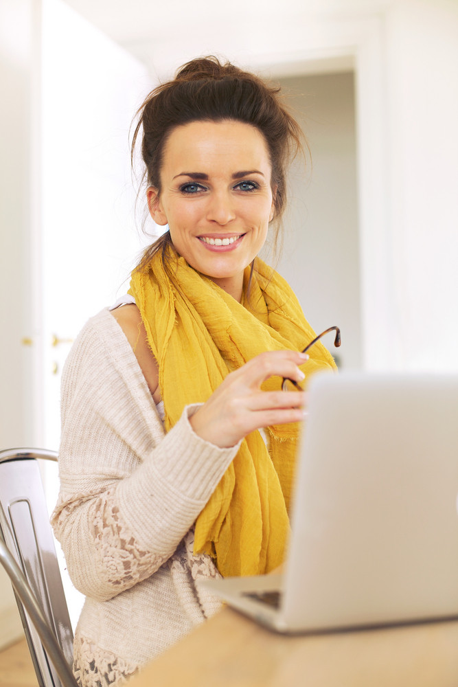 Confident woman at home sitting and looking happy