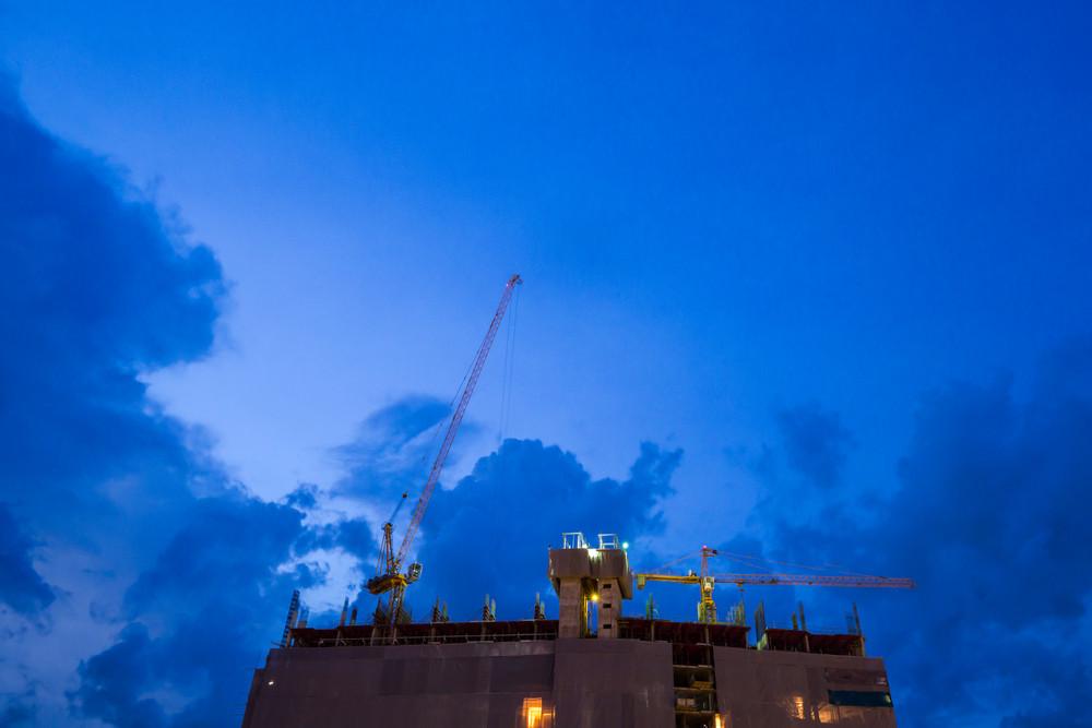 Construction crane on twilight sky.