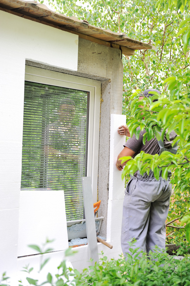 Construction worker applying styrofoam to exterior house wall