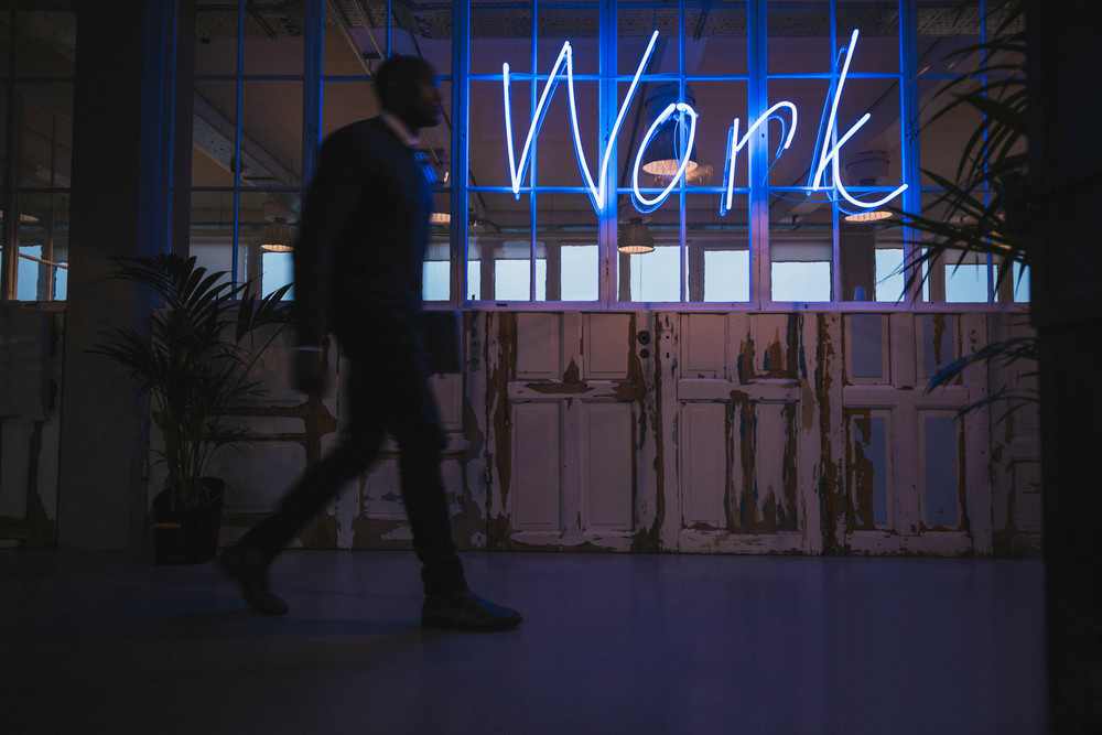 Corridor of modern office with young man walking by. Big neon light work sign.