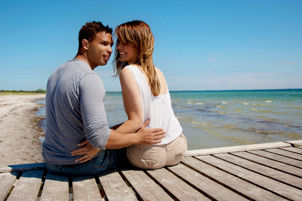 Couple sitting on a pier on a beautiful sunny day at the beach