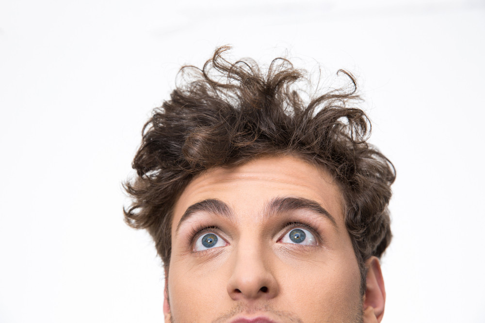 Crop image of a handsome young man with curly hair looking up at copyspace