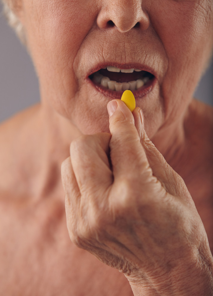 Cropped image of old woman taking a pill. Focus on hand and pill. Close-up of senior woman taking medication for good health.