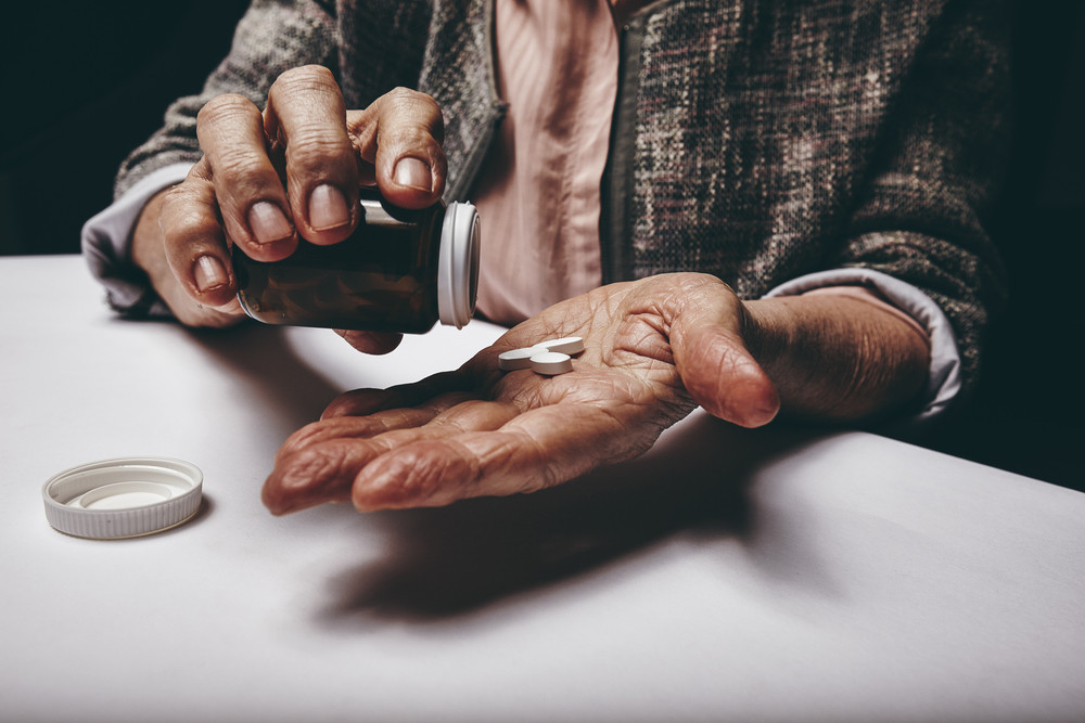 Cropped shot of a old woman sitting at a table shaking a pill out of a pill bottle. Focus on hands. Senior female taking medicine.