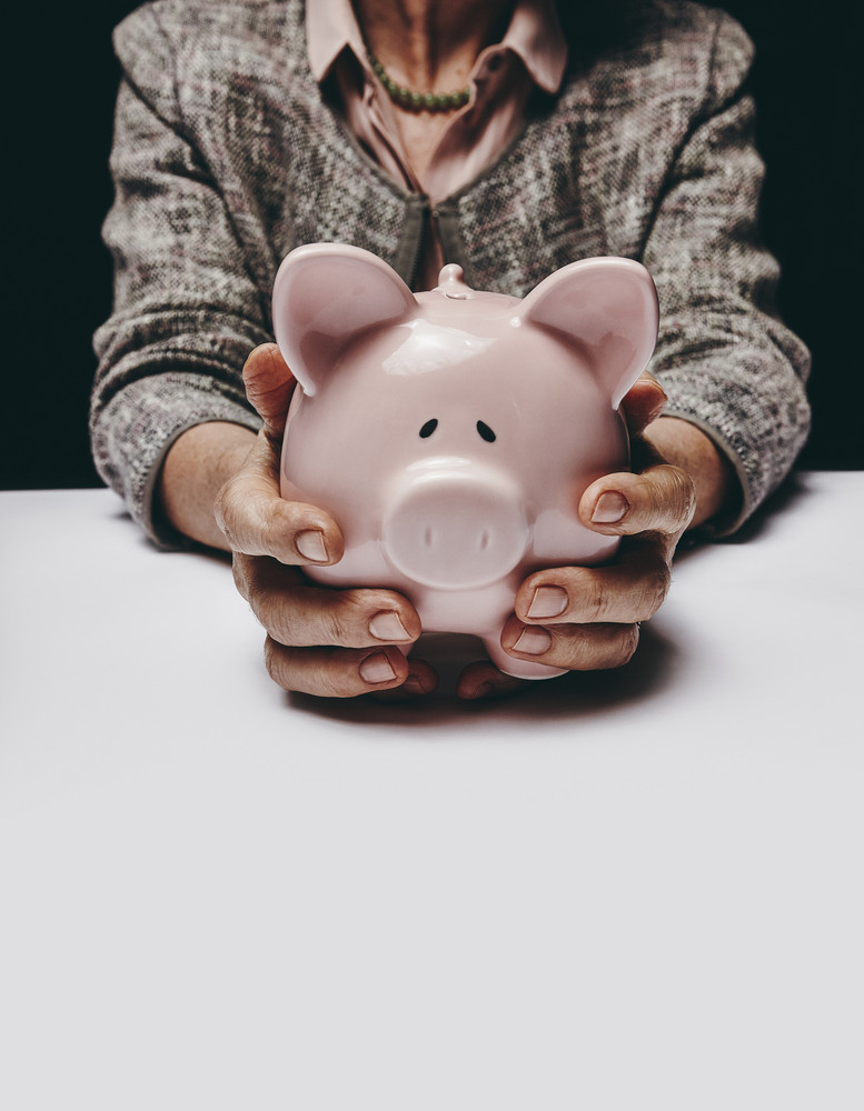 Cropped studio shot of senior female hands holding a coin bank while sitting at a table. Old woman holding a piggybank.