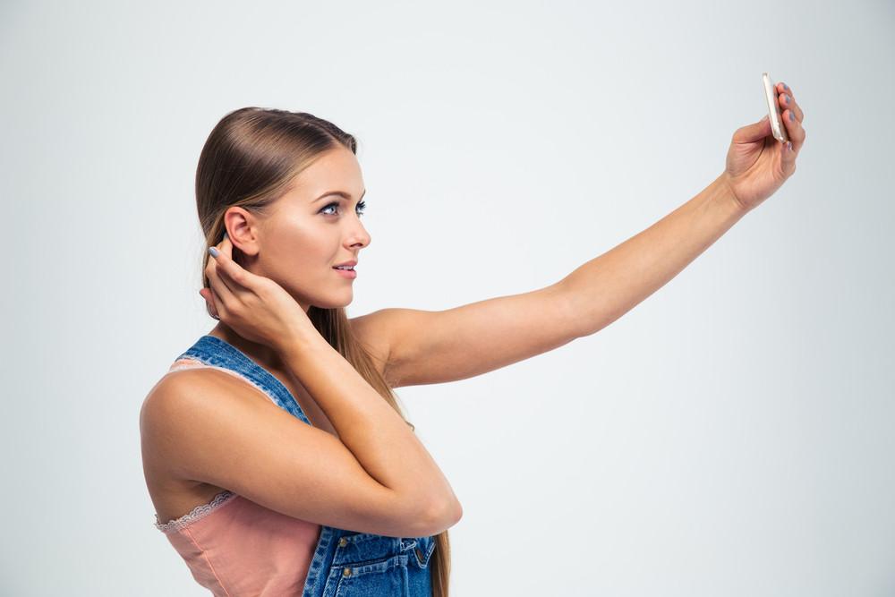 Cute girl making selfie photo on smartphone