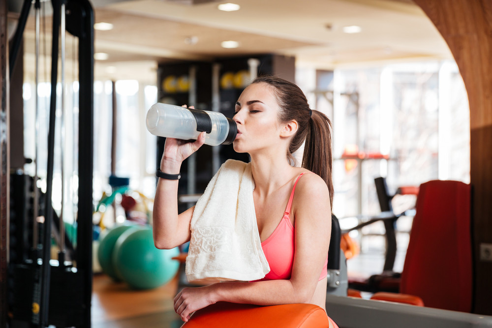 Cute lovely young woman athlete drinking water on training in gym