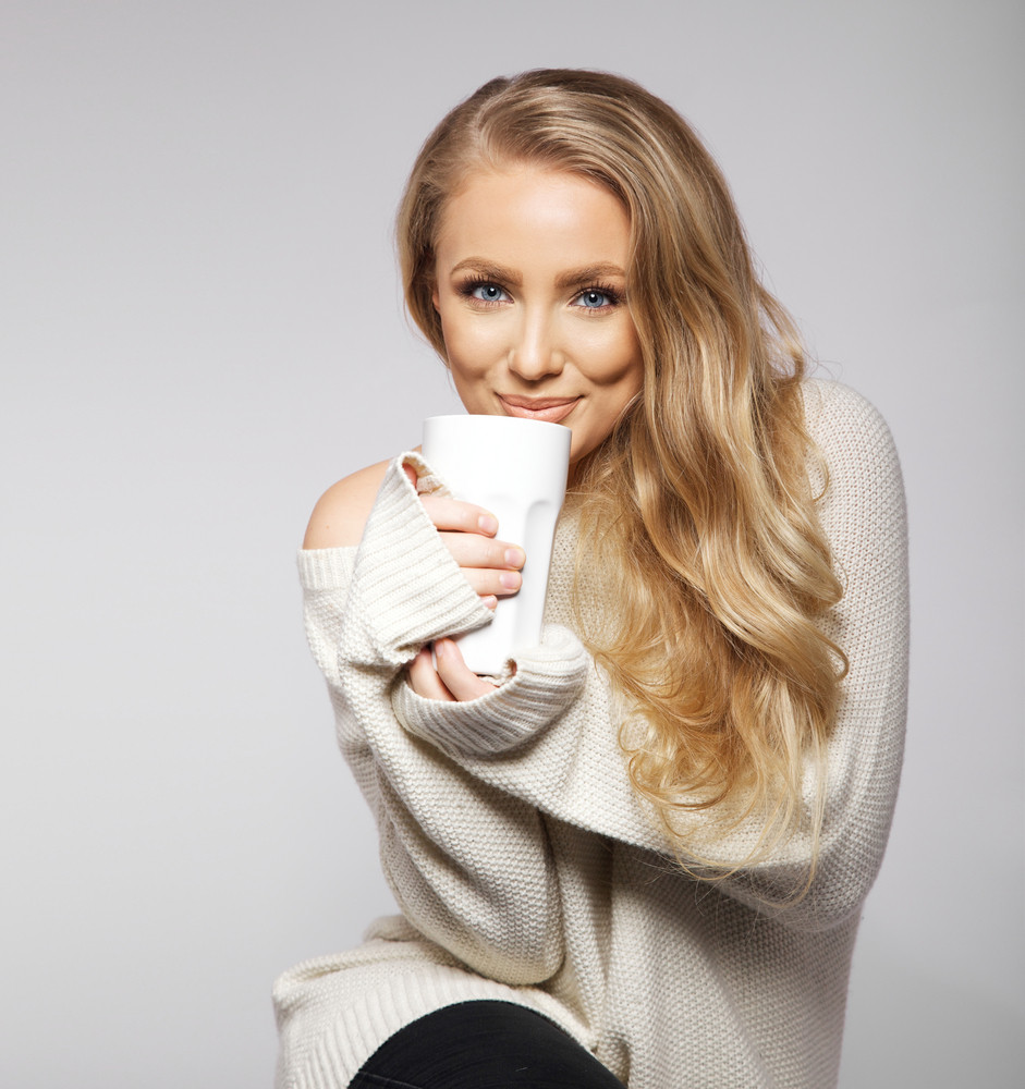 Cute smiling girl in oversized sweater. Lovely smiling young woman holding a cup of warm tea or coffee.