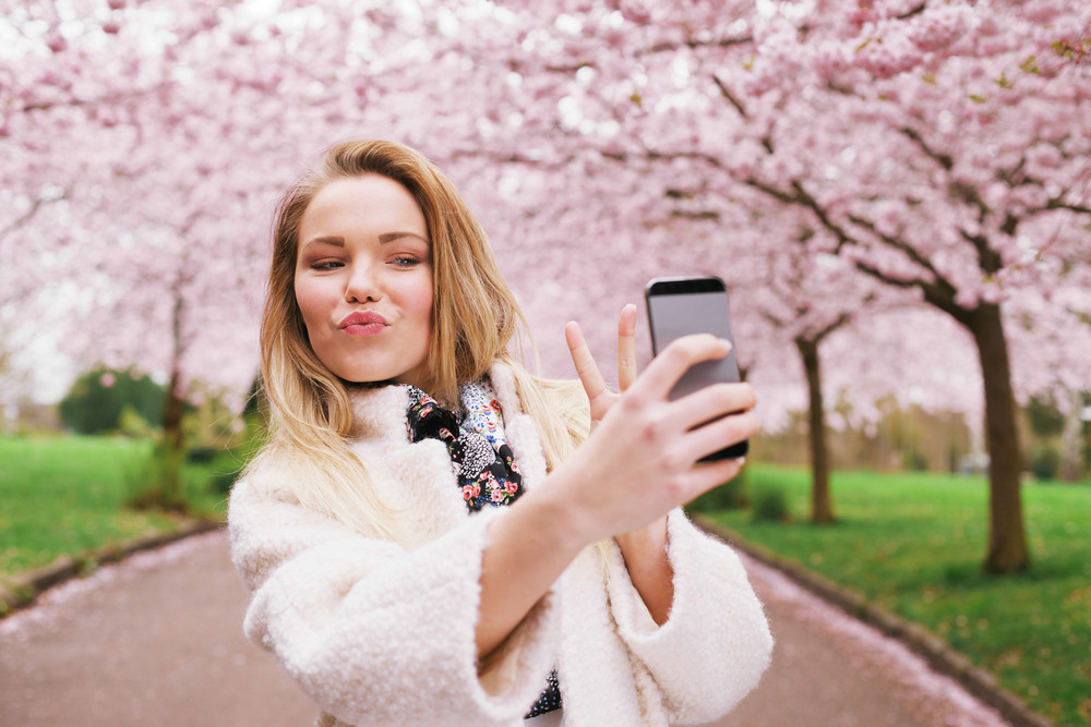 Cute young woman gesturing peace sign while taking her picture with mobile phone. Caucasian female model at spring blossom park taking self portrait with smart phone.