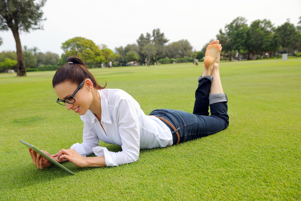 Beautiful Young Woman With  Tablet In Park