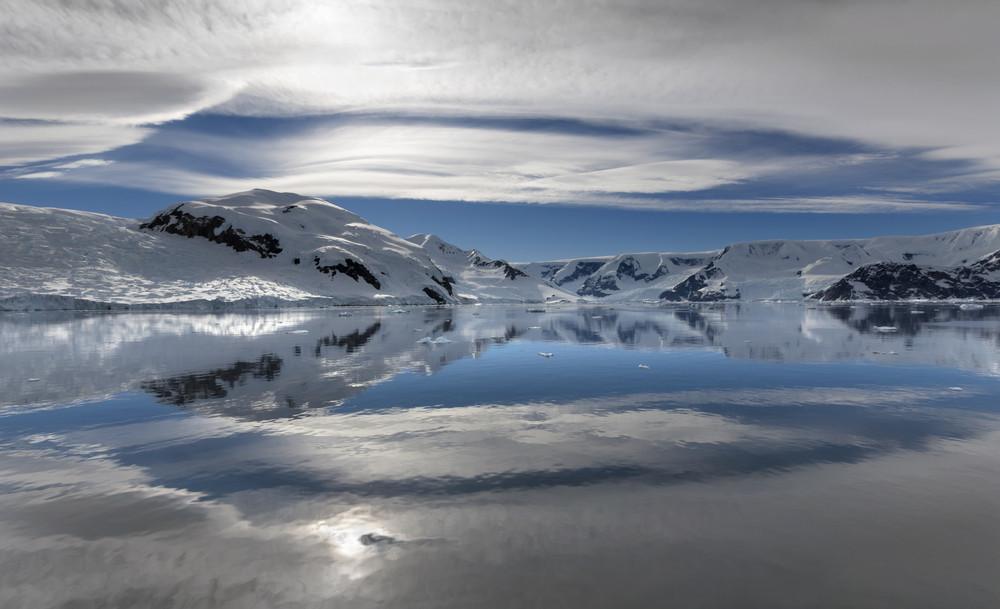 Sunlit, snowy coast reflected under a cloudy sky