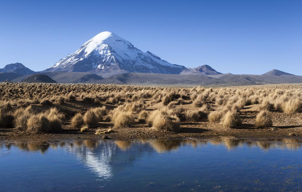 Flatland um córrego antes de uma montanha distante, coberta de neve