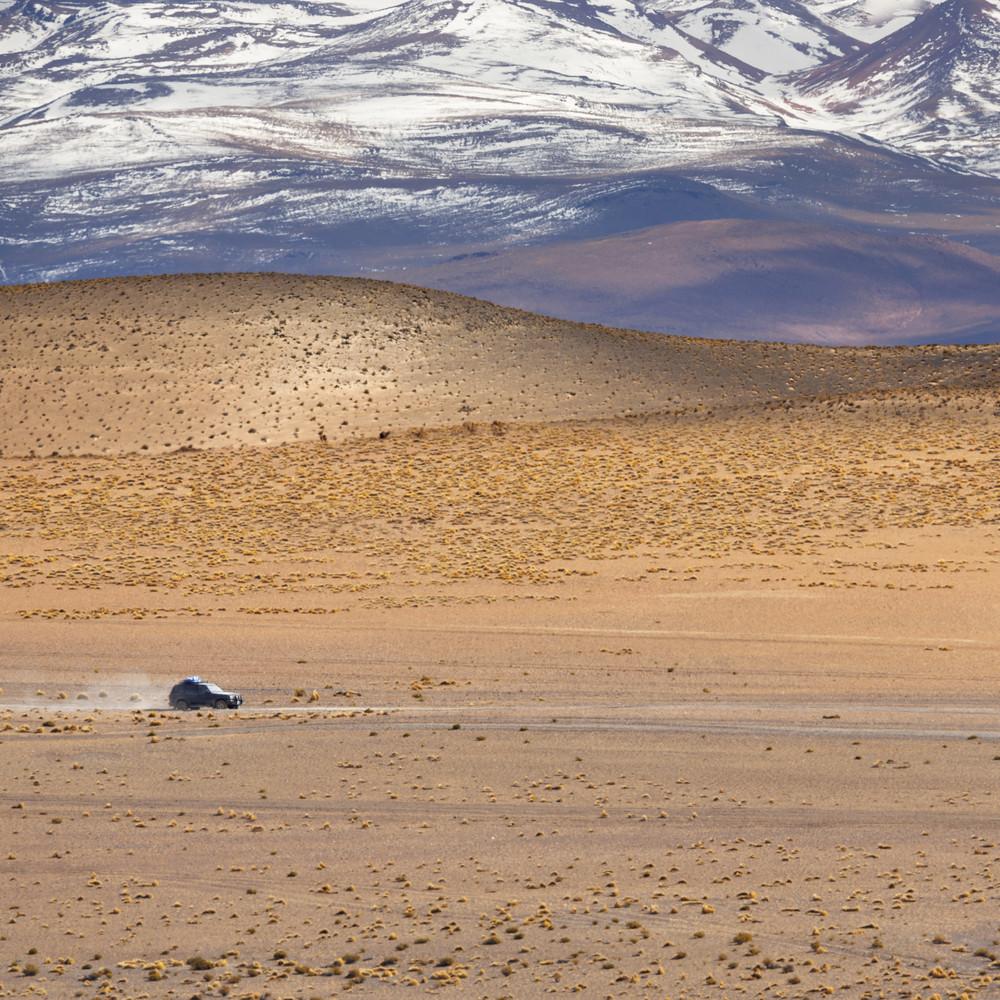 Car traveling through an arid, mountain landscape