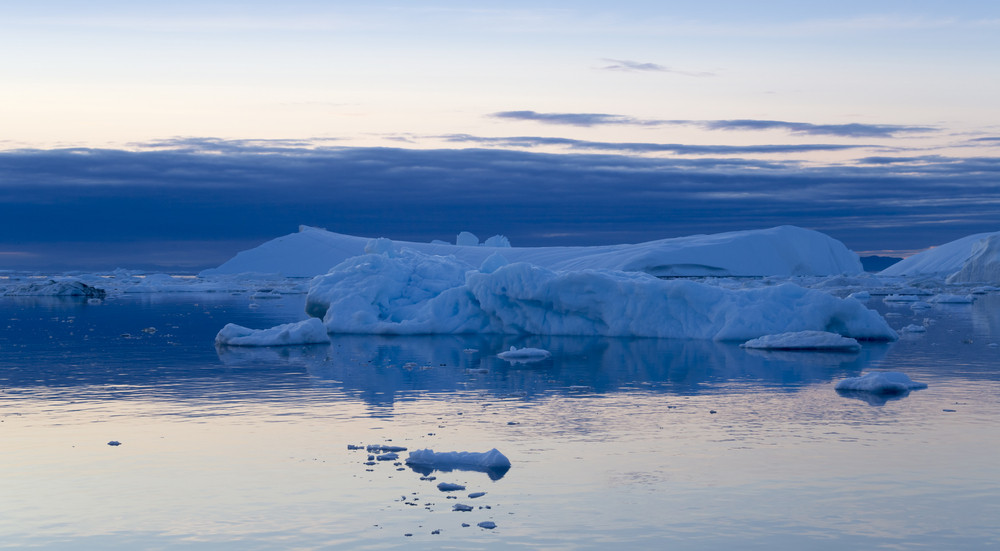 Iceberg in icy waters at dusk