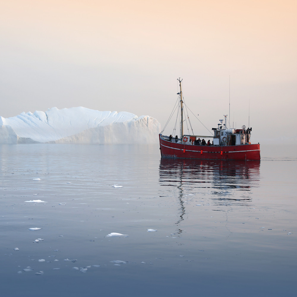 Red boat traveling past an iceberg at dawn Royalty-Free