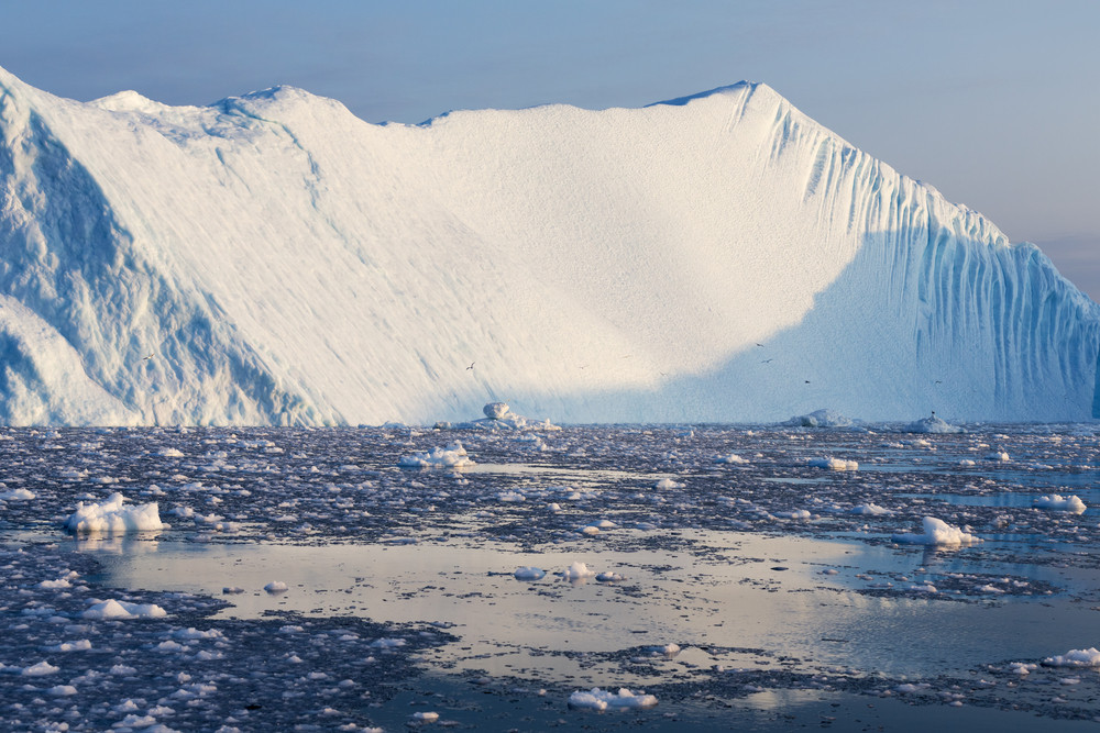 Sunlit iceberg in icy waters