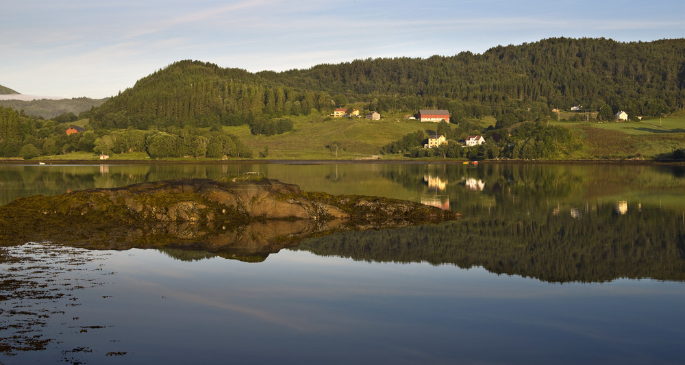 Farmland reflected in a still lake