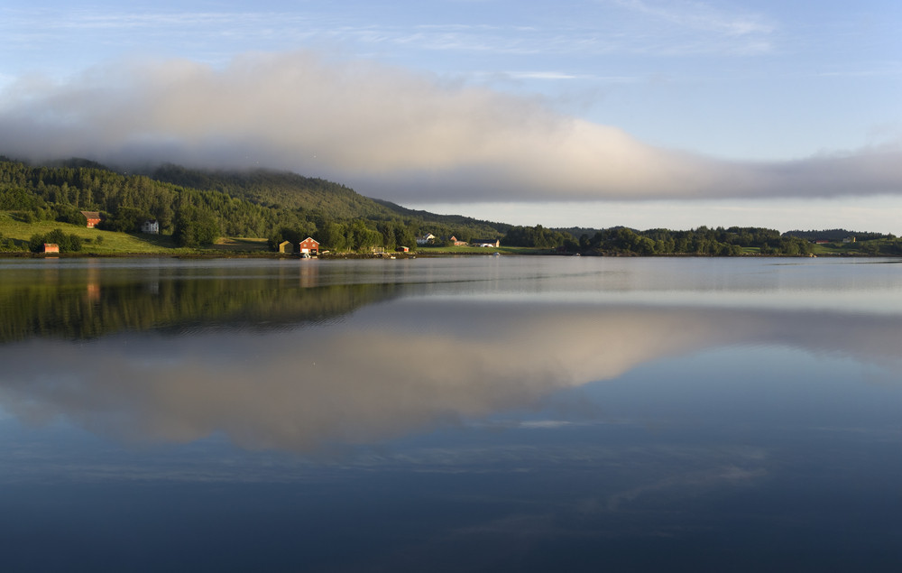 Mountains and farmland reflected in a lake at dawn