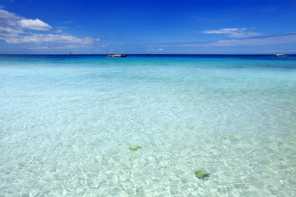 Distant boats on clear, tropical waters