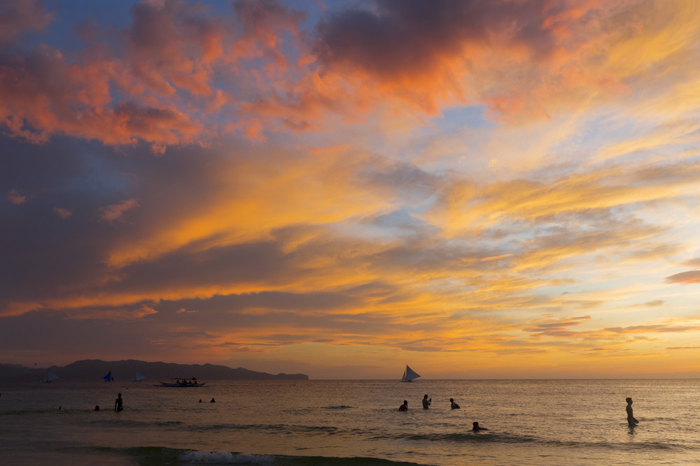 Swimmers in the ocean during a dramatic sunset