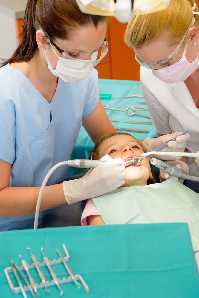 Dentist and nurse curing little girl at stomatology clinic
