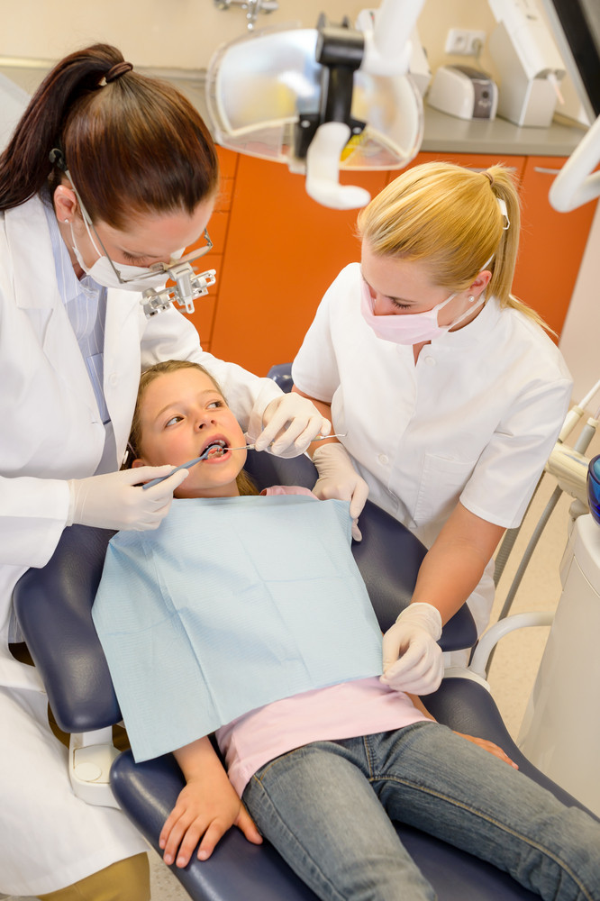 Dentist with nurse and little child have checkup at surgery