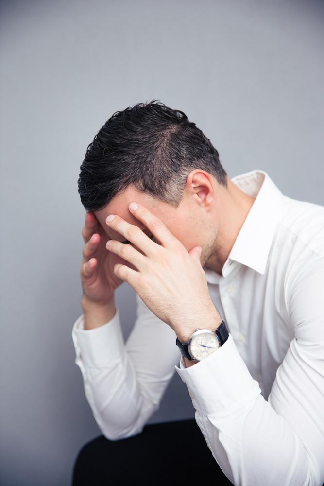 Depressed businessman over gray background