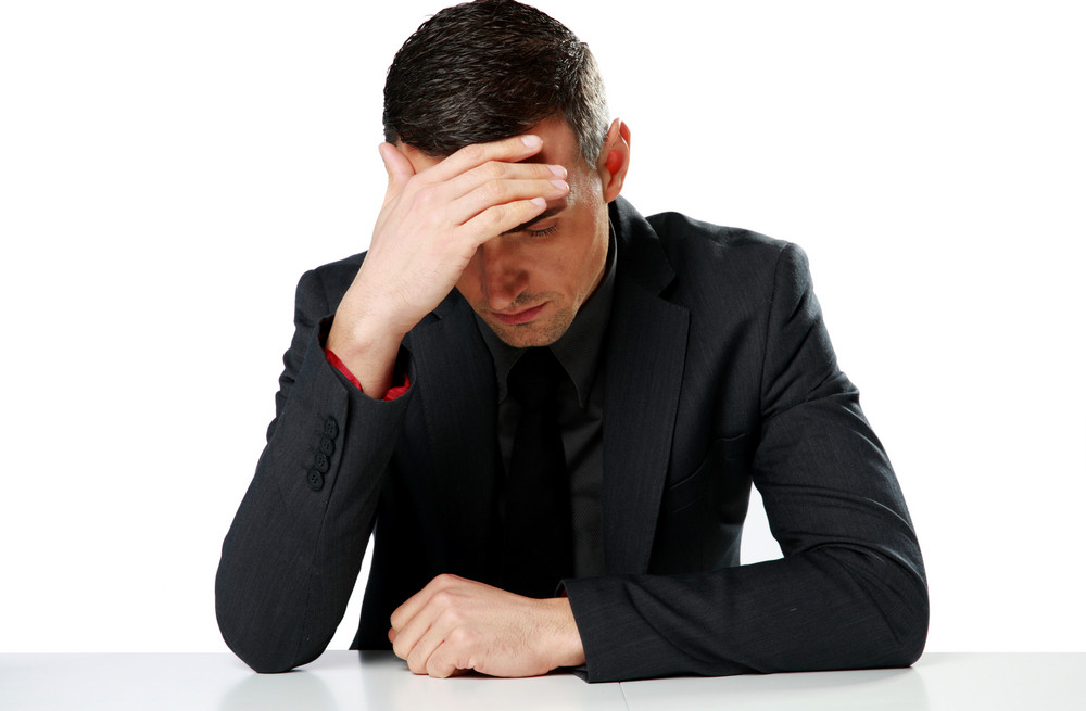 Depressed businessman sitting at the table isolated on a white background