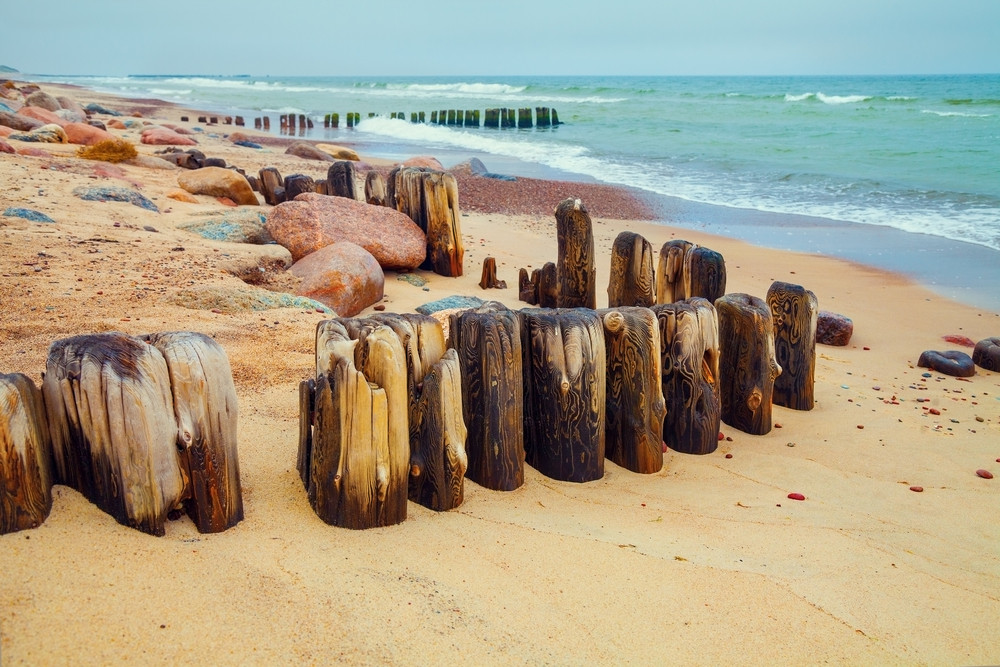 Desert beach with old wooden column