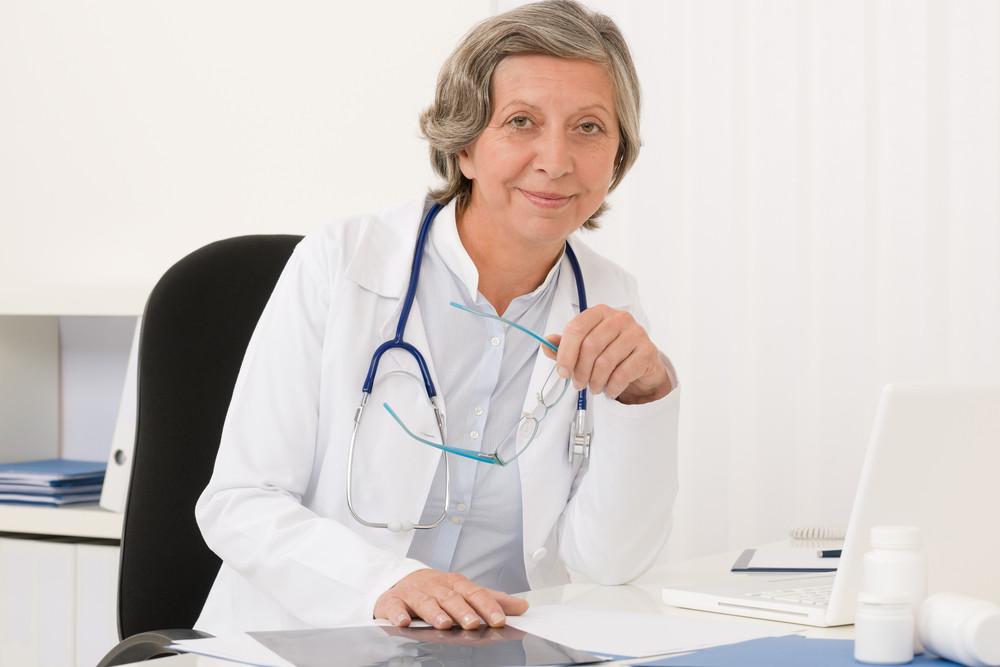 Doctor office - senior female physician work computer sit behind desk
