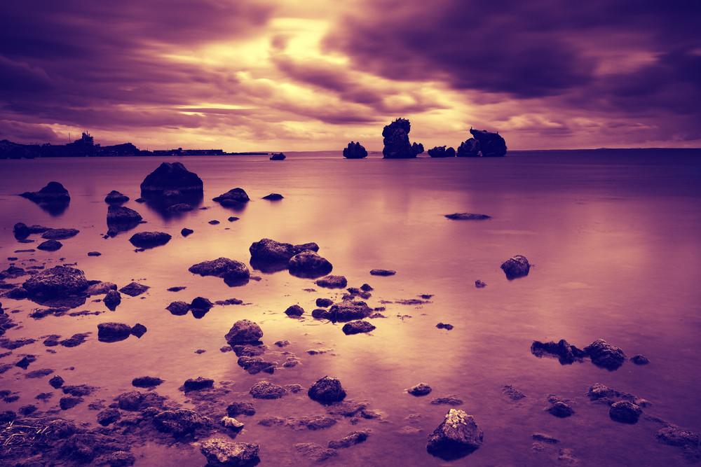 Dramatic cloudy sky before sunrise over a rocky seashore