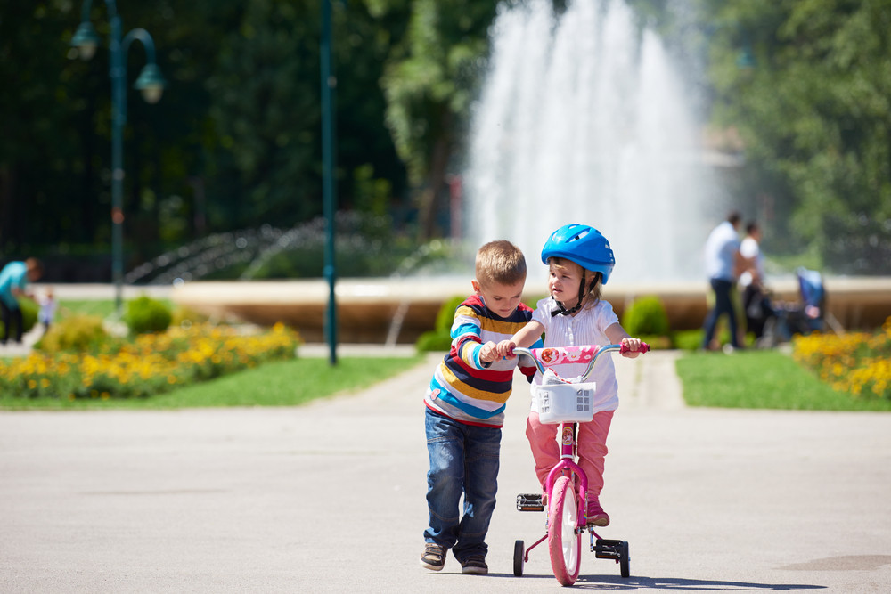 Brother And Sister In Park Have Fun. Boy And Girl In Park Learning To Ride A Bike.