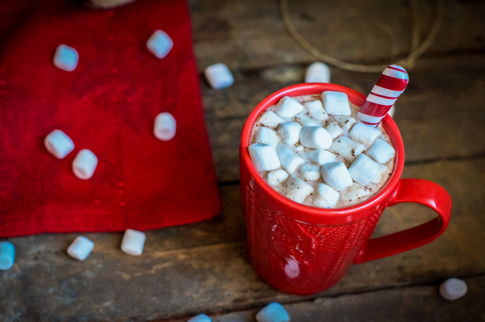 Red Knitted Mug Filled With Hot Chocolate And Marshmallows On Wooden Background