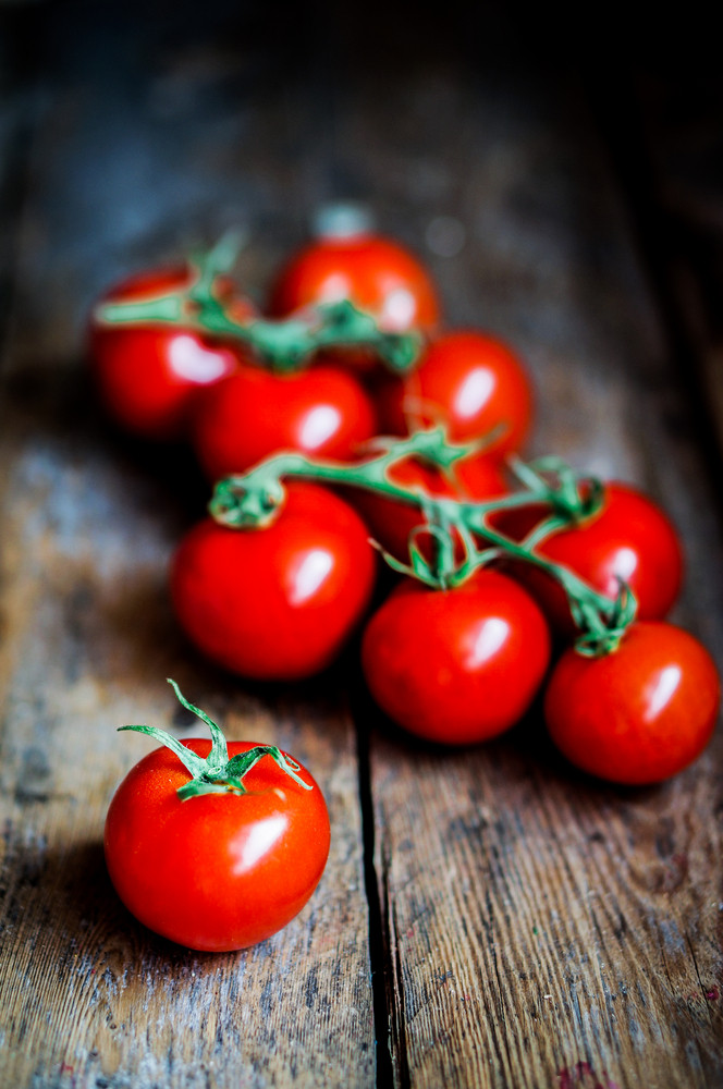 Tomatoes On The Vine On Rustic Wooden Background