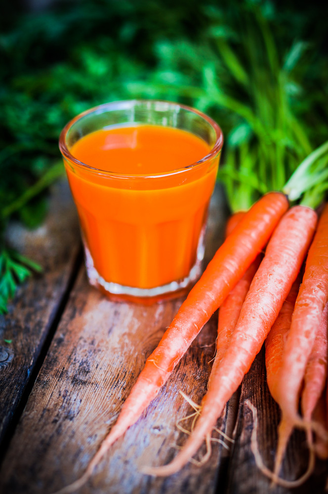 Fresh-squeezed Carrot Juice On Wooden Background
