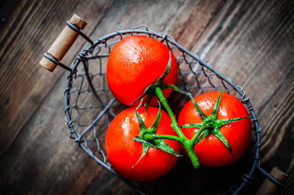 Fresh Tomatoes In Antique Basket On Wooden Background