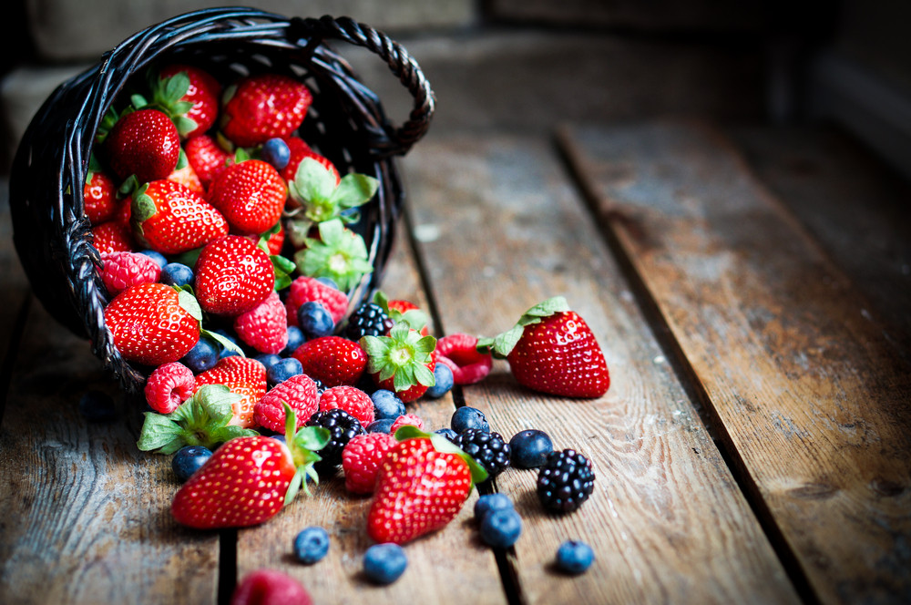 Mix Of Fresh Berries In A Basket On Rustic Wooden Background
