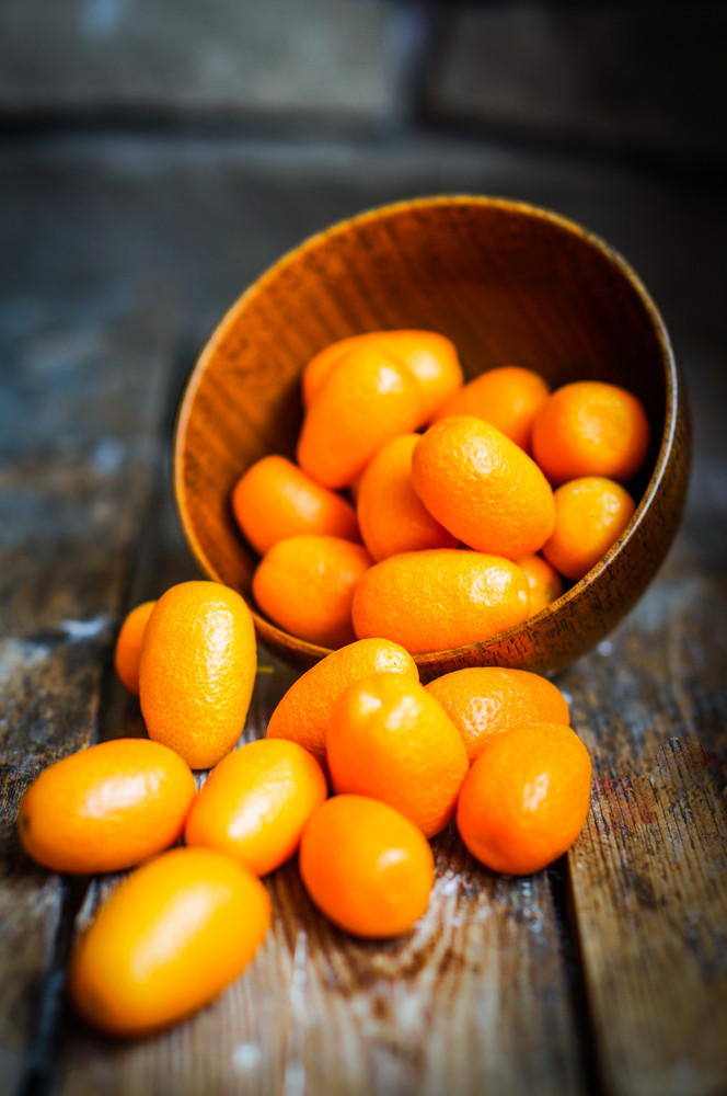 Kumquat In A Bowl On Rustic Wooden Table