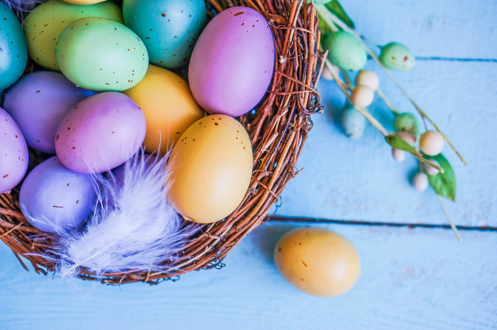 Easter Eggs In The Nest On Blue Wooden Background