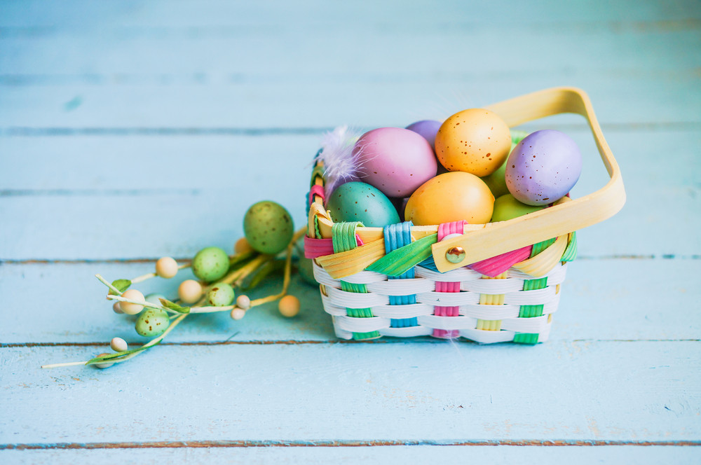 Easter Eggs In The Basket On Blue Wooden Background
