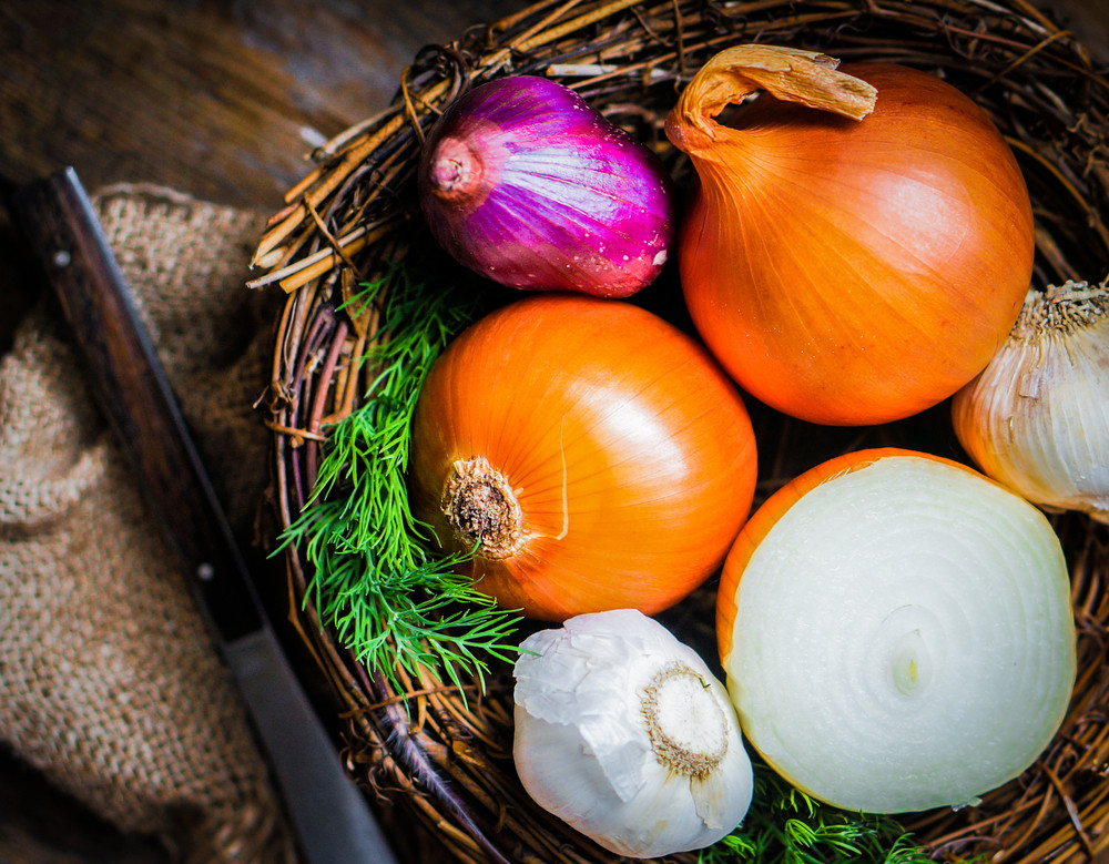 Colorful Onions And Garlic In The Basket On Rustic Wooden Background
