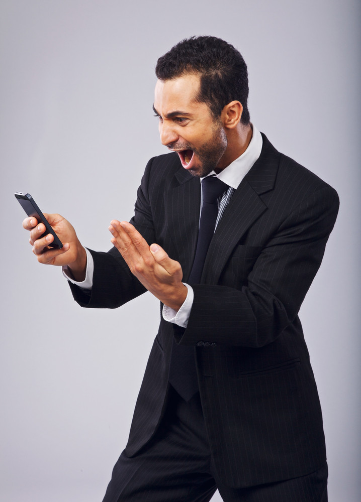 Ecstatic businessman screaming in excitement while reading sms from his cell phone