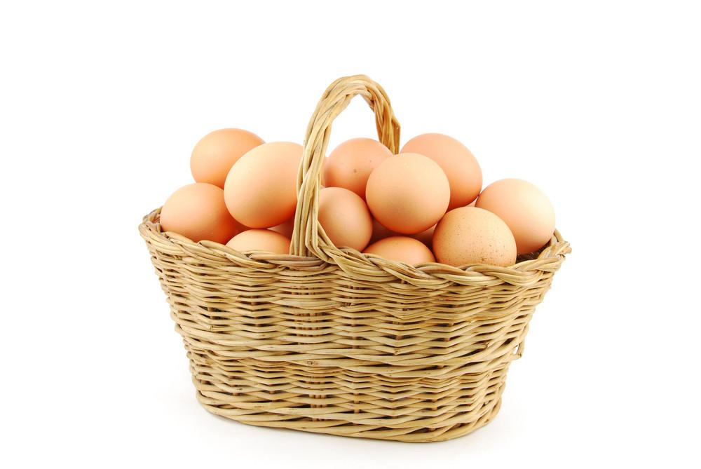 Eggs In A Wicker Basket On White