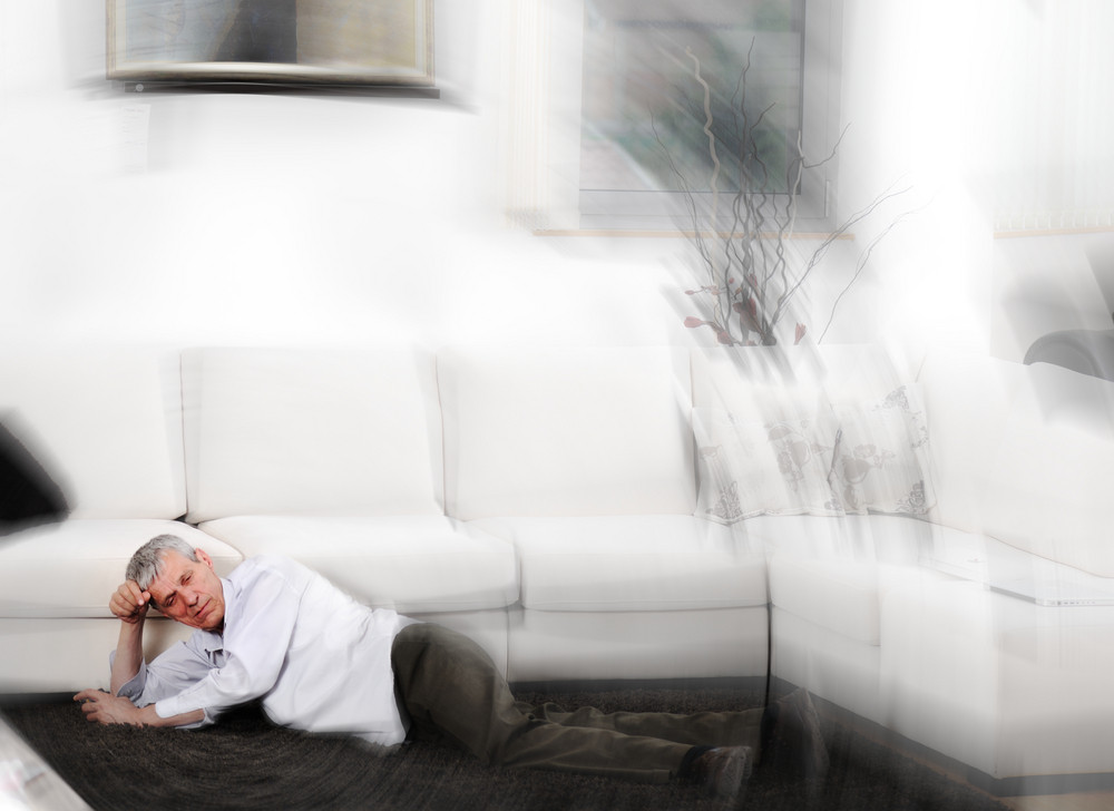 Elderly man having heart attack lying on floor at home