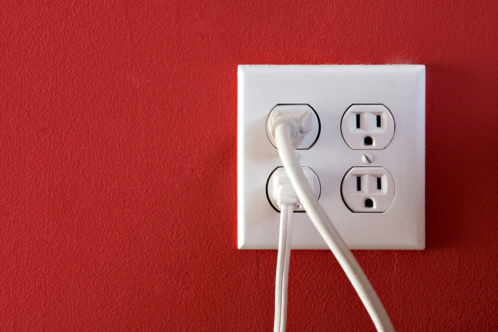 Electrical outlets with four spaces and two of them have chords plugged in.
