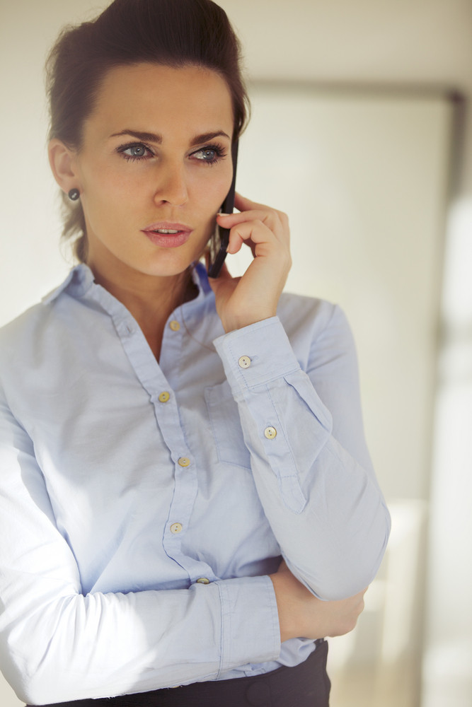 Elegant young woman talking business on the phone. Beautiful caucasian female in blue shirt looking away using phone.