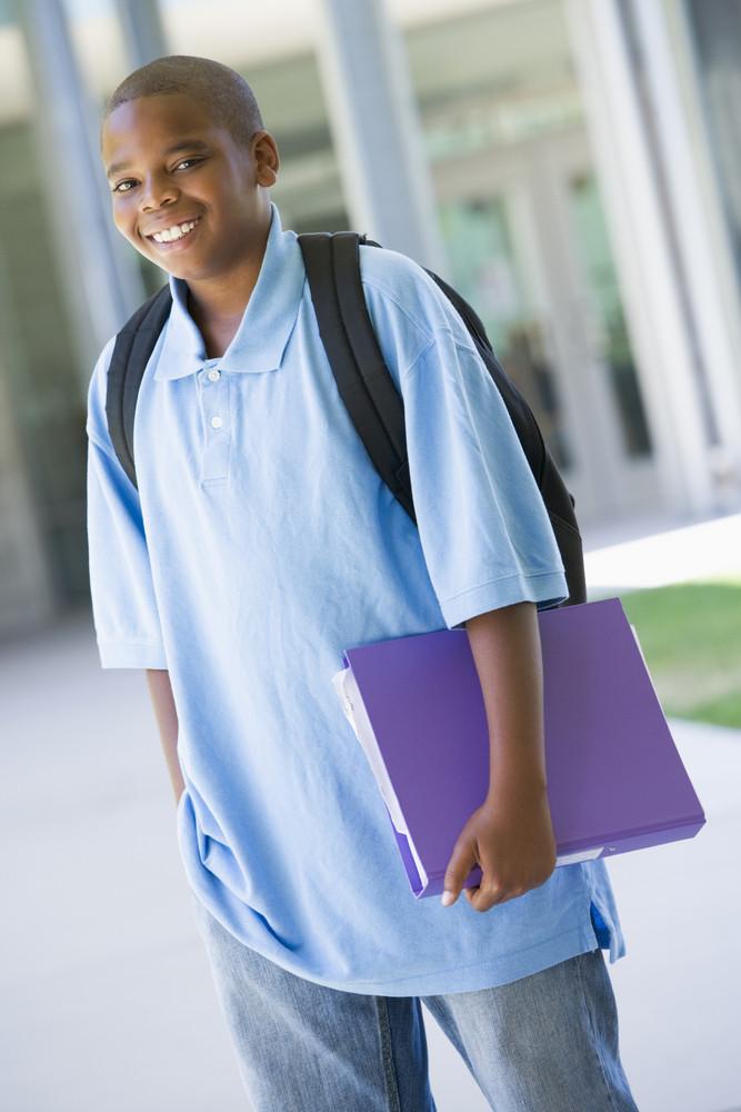 Elementary school pupil outside carrying folder