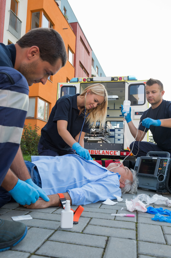 Emergency team helping injured elderly patient lying on ground