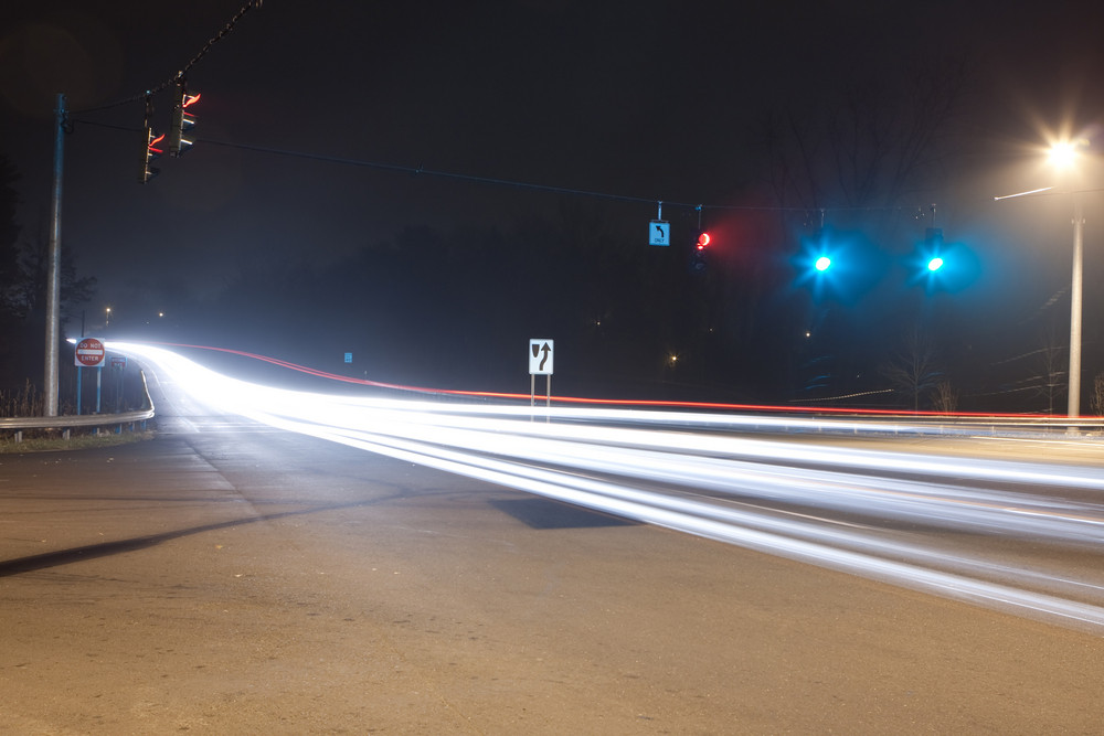Evening traffic creates abstract trails of light from cars as they drive down the roadway in this long exposure image.