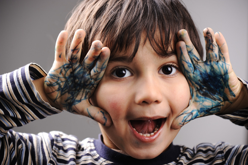 Excited little boy with messy color hands